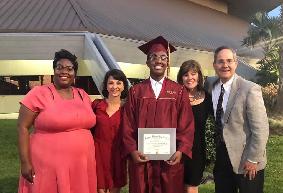 Proud graduate with teachers